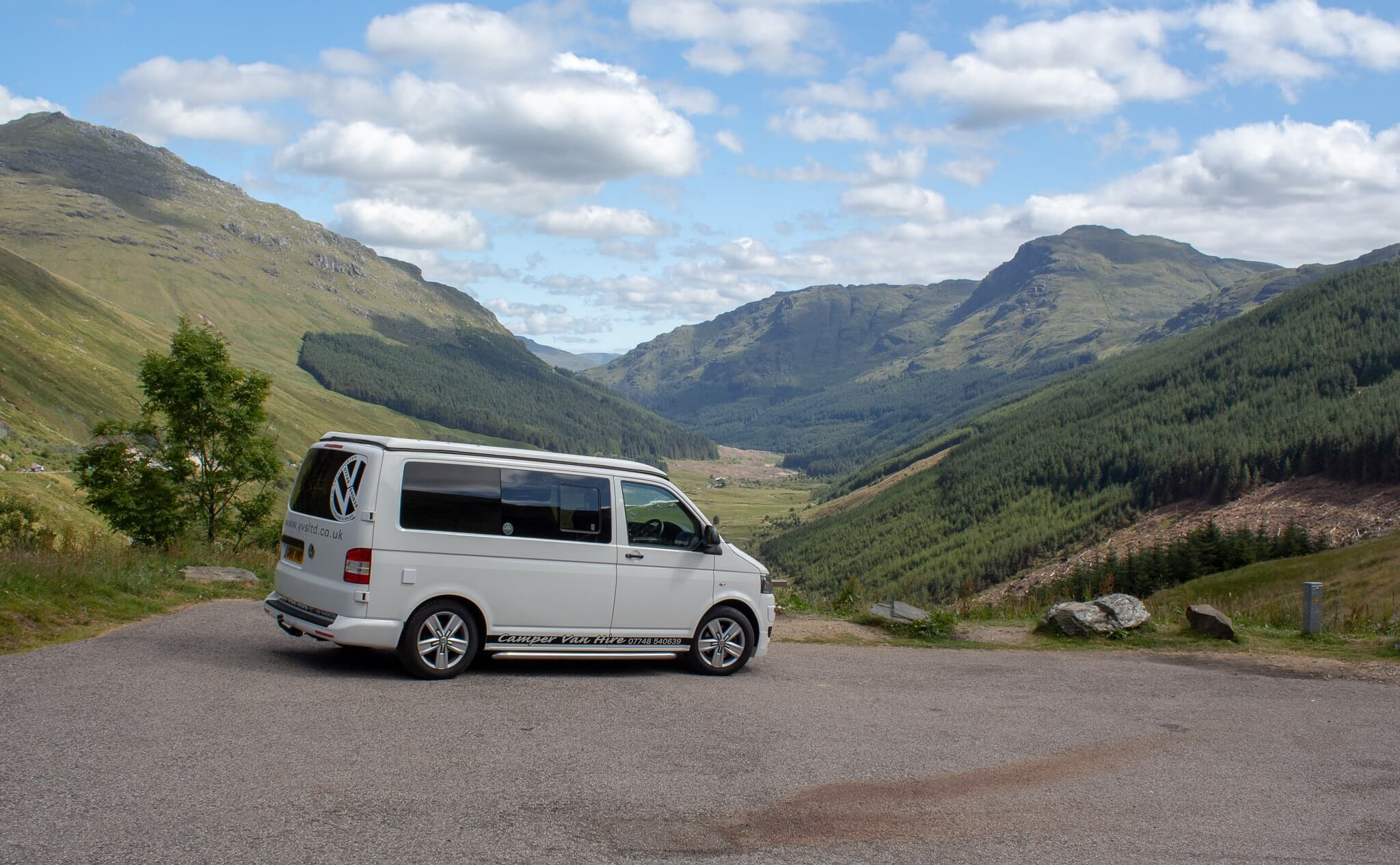 White Camper Van in Scotland at teh rest and be Thankful visitors stop with scottish mountains in teh background