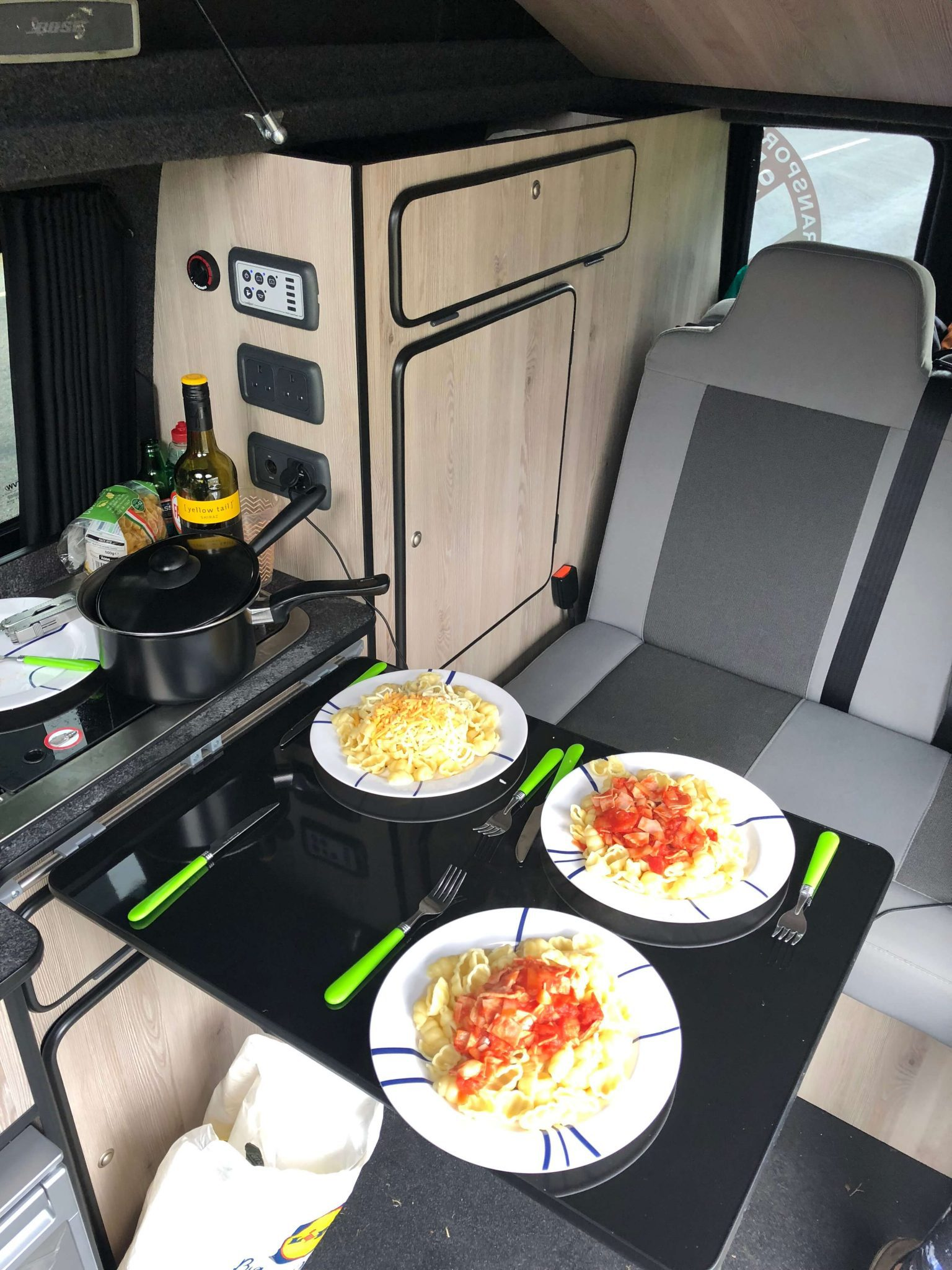 Camper van cooking in a VW Camper van with the table set ready to eat enjoying the views of Kilchurn Castle